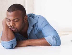 Black businessman sleeping at desk